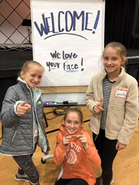 "students smiling with ""We love your face"" sign"